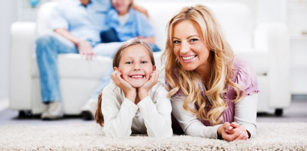 smiling mother and daughter laying on carpet